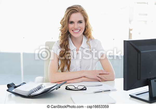 Smiling businesswoman with computer in office - csp16653359