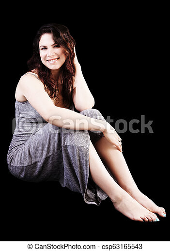 Smiling Caucasian Woman Sitting In Grey Dress On Black Background - csp63165543
