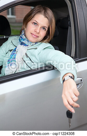 Smiling Caucasian woman sitting in land vehicle with car key - csp11224308