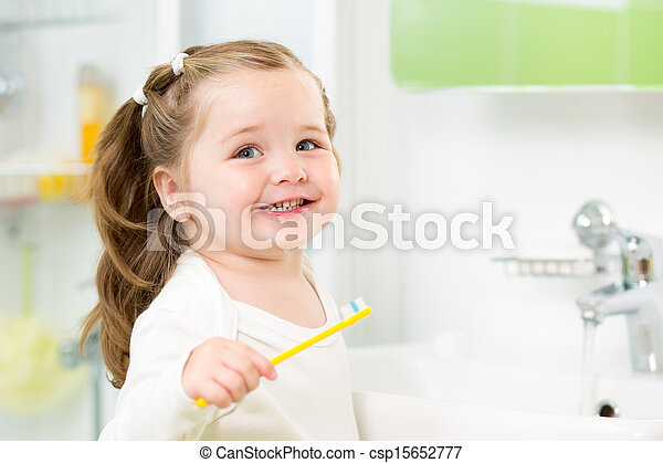 Smiling child girl brushing teeth in bathroom - csp15652777