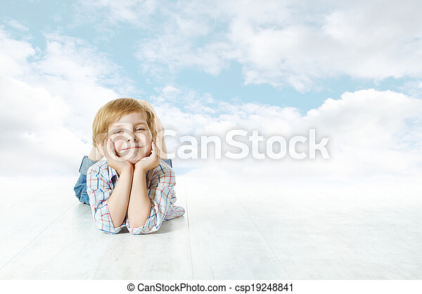 Smiling child lying down, small kid looking at camera. Blue sky and clouds - csp19248841