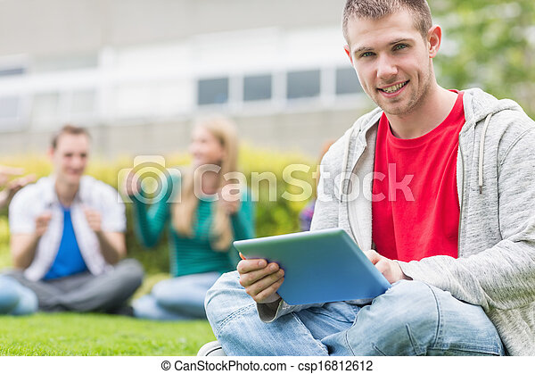 Smiling college boy holding tablet PC with students in park - csp16812612