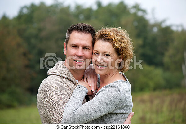 Smiling couple hugging outdoors - csp22161860