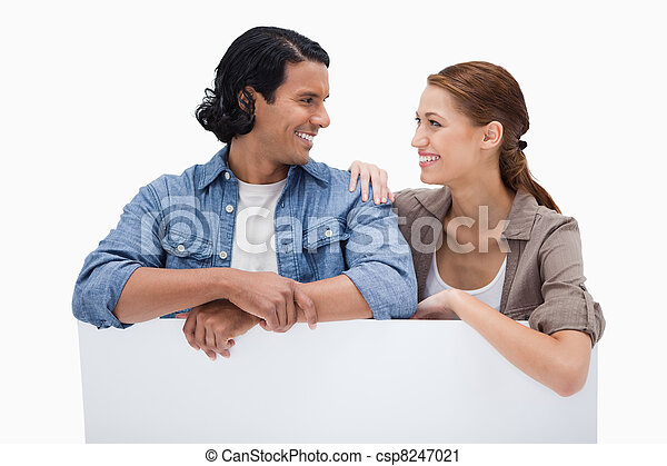 Smiling couple leaning on blank wall - csp8247021