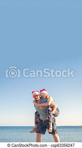 158924a1 Smiling couple piggybacking in christmas hats and sunglasses at the beach  of the sea.
