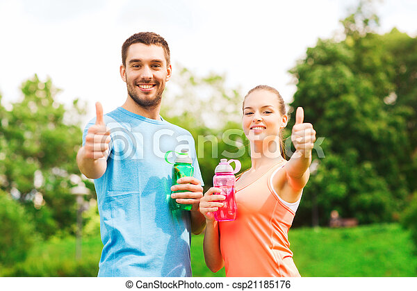 smiling couple with bottles of water outdoors - csp21185176