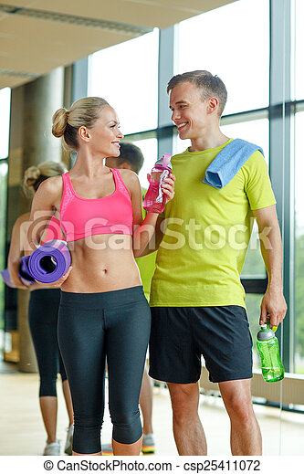 smiling couple with water bottles in gym - csp25411072