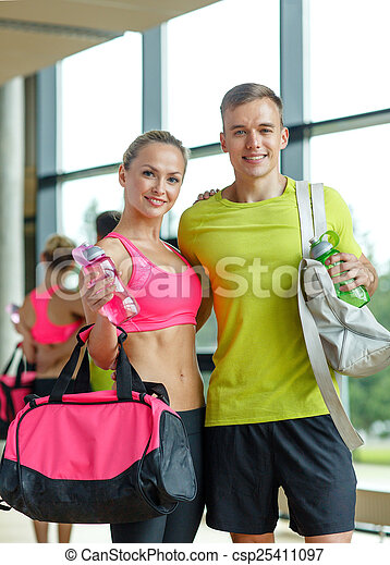 smiling couple with water bottles in gym - csp25411097