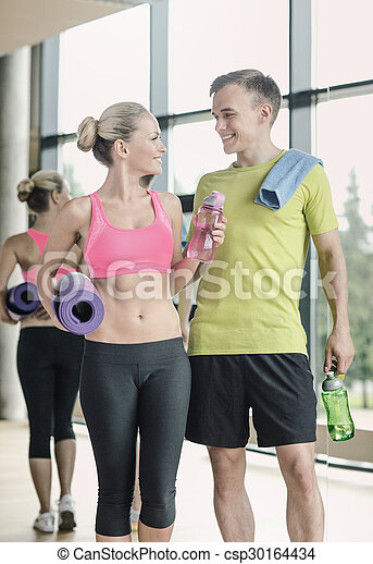smiling couple with water bottles in gym - csp30164434