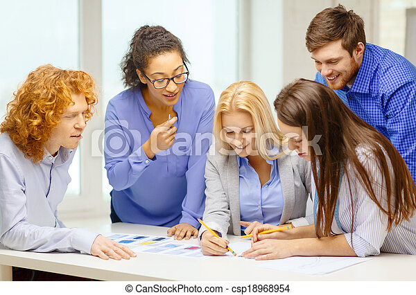 smiling creative team looking over clothes designs - csp18968954