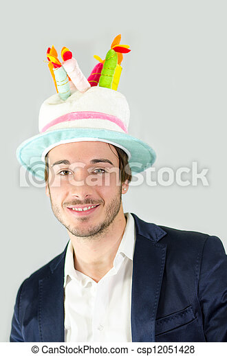 Smiling, cute guy with funny birthday cake hat - csp12051428