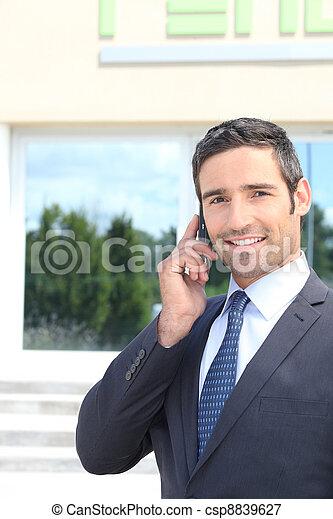 Smiling director using mobile phone - csp8839627