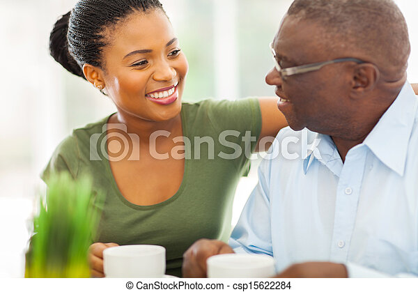 smiling elderly african american man enjoying coffee with his granddaughteer at home - csp15622284