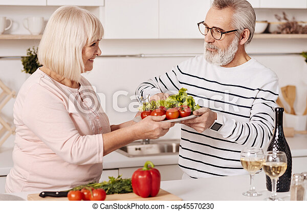 Smiling elderly couple preparing family dinner together in the kitchen - csp45570230