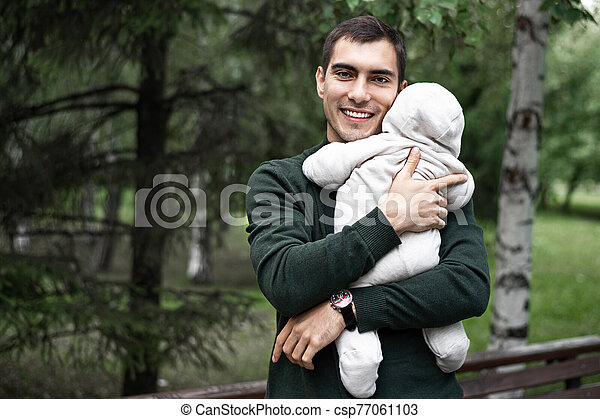 smiling father brunette in green jacket with baby in his arms on walk in the Park - csp77061103