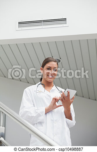 Smiling female doctor using a tablet computer - csp10498887