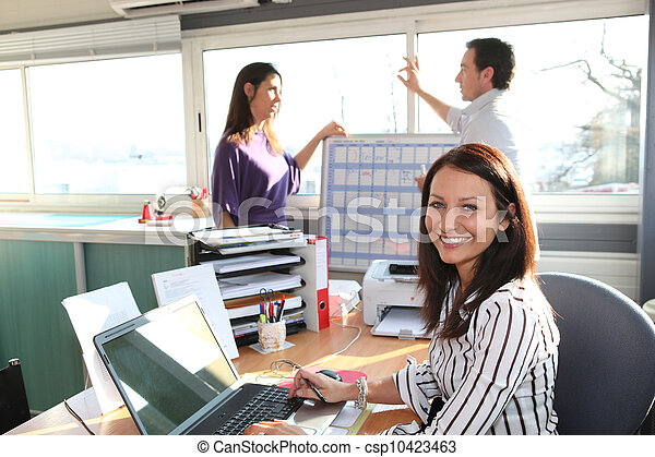 smiling female employee in office and colleagues in background - csp10423463