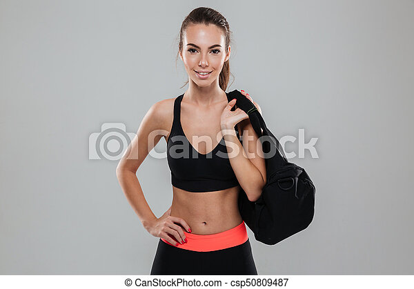 eeda9912 Smiling fitness woman with bag holding arm on hip and looking at the ...