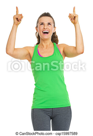 Smiling fitness young woman pointing up on copy space - csp15997589