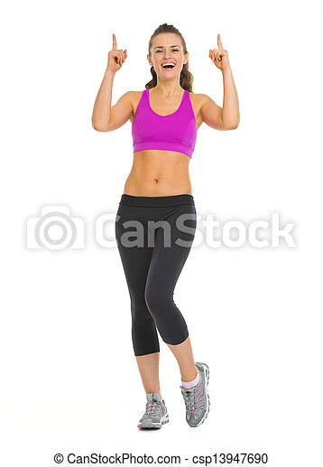 Smiling fitness young woman pointing up on copy space - csp13947690