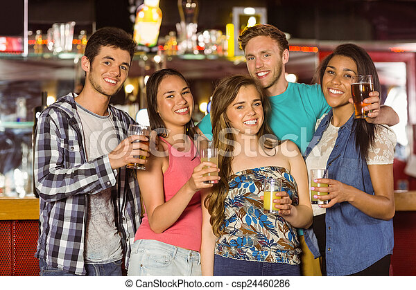 Smiling friends drinking beer and mixed drink - csp24460286