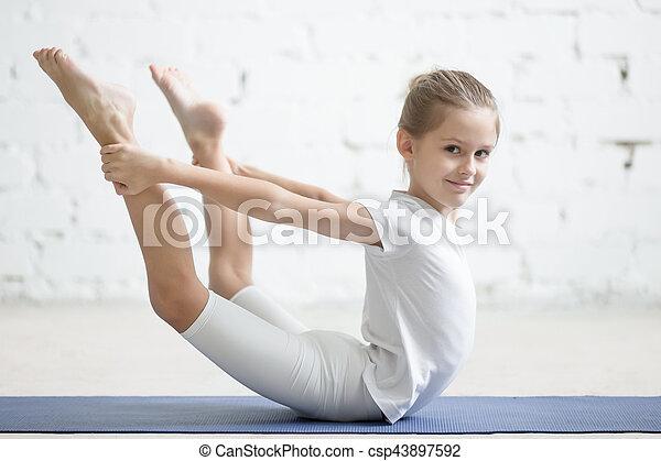 smiling girl child in dhanurasana pose white studio