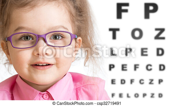 Smiling girl putting on glasses with blurry eye chart behind her - csp32719491