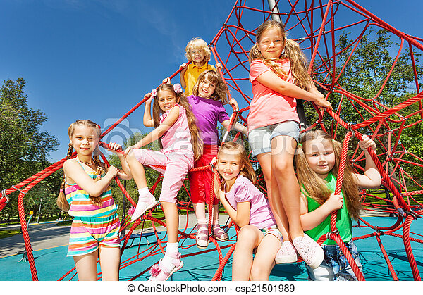 Smiling group of children sit on red ropes - csp21501989