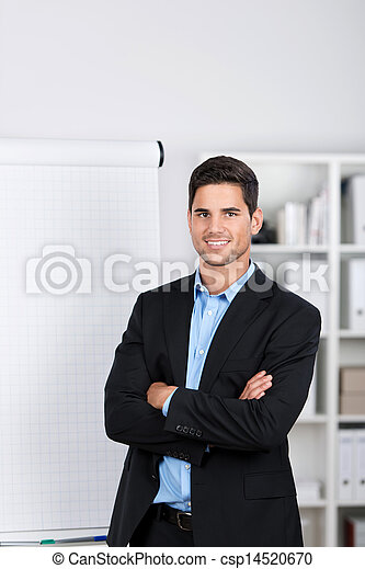 Smiling handsome businessman near a flip-chart - csp14520670