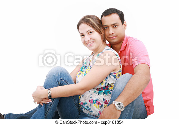 smiling happy couple sitting down next to wall - csp8161854