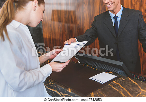 Smiling hotel worker helping his guest - csp42742853