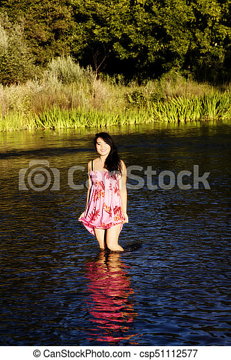 Smiling Japanese American Woman Standing In River - csp51112577