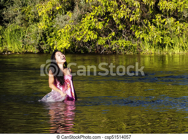 Smiling Japanese American Woman Standing In River - csp51514057