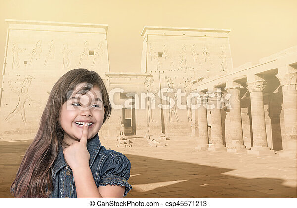 Smiling little girl is standing in front of Philae temple. - csp45571213