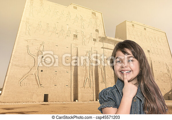Smiling little girl is standing in front of Edfu temple. - csp45571203