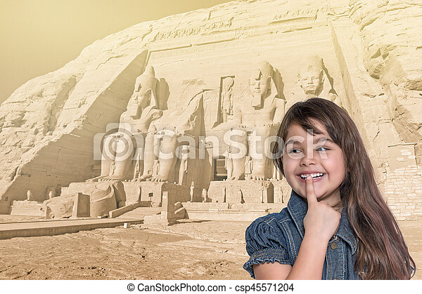 Smiling little girl is standing in front of Abu Simbel temple. - csp45571204