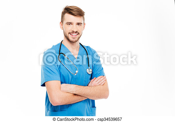 Smiling male doctor standing with arms folded  - csp34539657