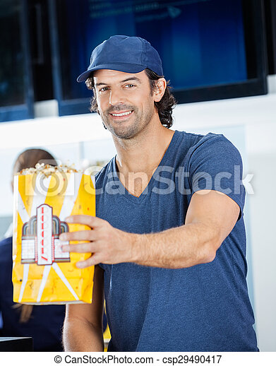 Smiling male worker offering popcorn at concession stand.... stock ...