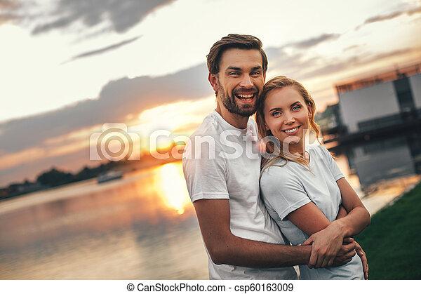2465528ba88 Smiling man hugging pleased girl near river. Portrait of cheerful ...