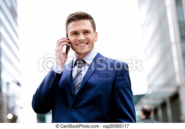 Smiling man in suit talking on cell phone - csp20565117