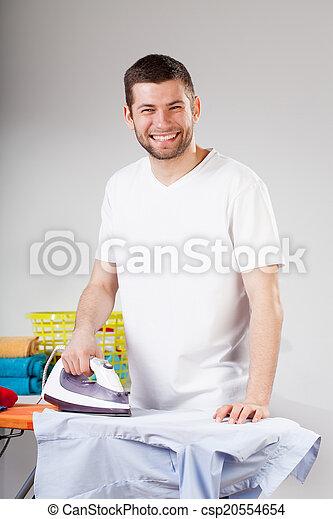 Smiling man ironing - csp20554654
