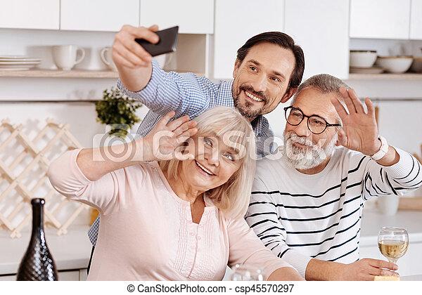 Smiling man taking selfie with senior parents at home - csp45570297