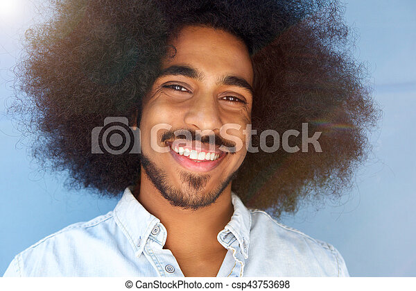 smiling man with afro and beard by blue wall - csp43753698