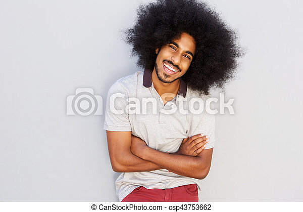smiling man with afro standing with arms crossed - csp43753662