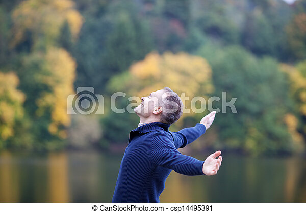 Smiling Man With Arms Outstretched Against Lake - csp14495391