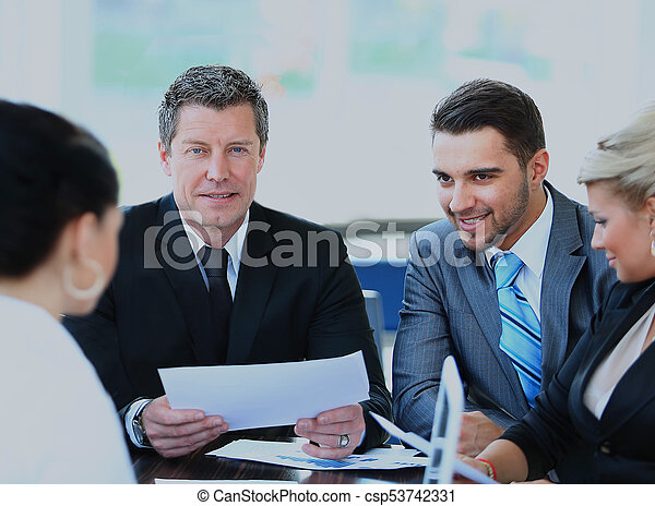 Smiling mature man sitting at a business meeting with colleagues. - csp53742331