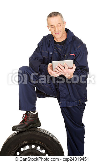 Smiling mechanic with a tire and tablet - csp24019451