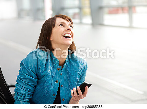 Smiling middle aged woman with cell phone - csp30685385