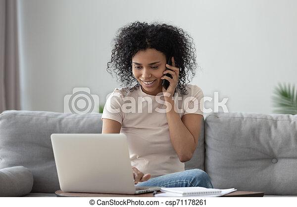 Smiling millennial african american woman talking on phone using laptop - csp71178261