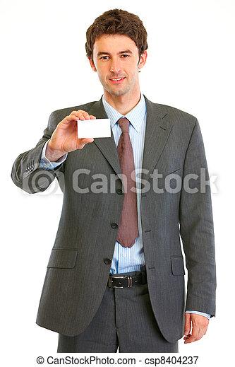 Smiling modern businessman showing business card - csp8404237